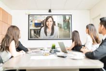 Colleagues Watching Presentation In Meeting Room