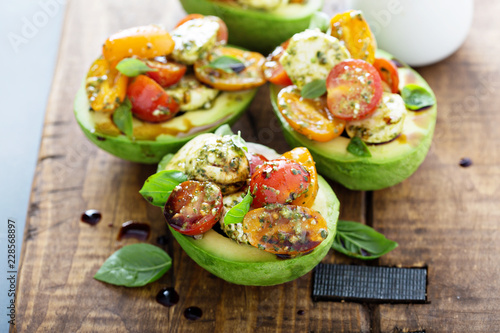 Fototapeta Avocado stuffed with pesto caprese salad obraz