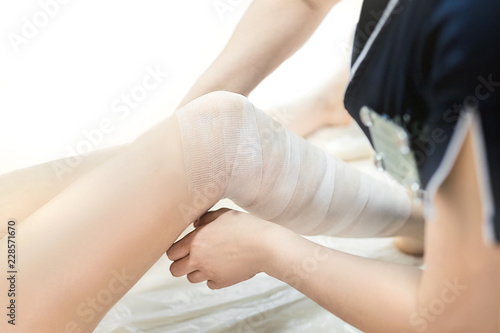 Foto Beautician wraps the leg of the patient in a white bandage