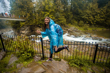 Young Girl In Blue Raincoat Stands In Rain By River