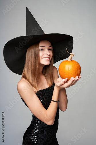 Fototapeta Smiling Halloween witch holding orange pumpkin, isolated on grey background