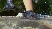 CLOSE UP: Unrecognizable Woman Hiking On Sunny Day Steps Out Of Glassy River.