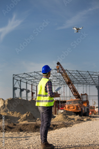 Construction worker with drone at building site Wall mural