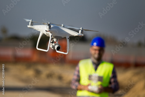 Obraz Construction worker with drone at building site - fototapety do salonu