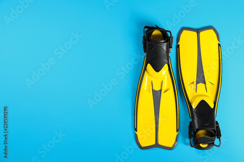 Swimming flippers on color background, top view. Space for text