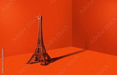 Poster de jardin Tour Eiffel Eiffel tower in an orange room. Minimalistic concept, travel and sightseeing. A metal statue of the Eiffel Tower on a strong orange background.