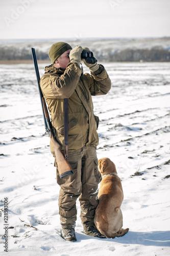 Охотник смотрит в бинокль с собакой