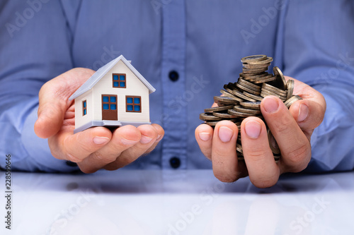 Fotografía  Man Holding House Model And Coins