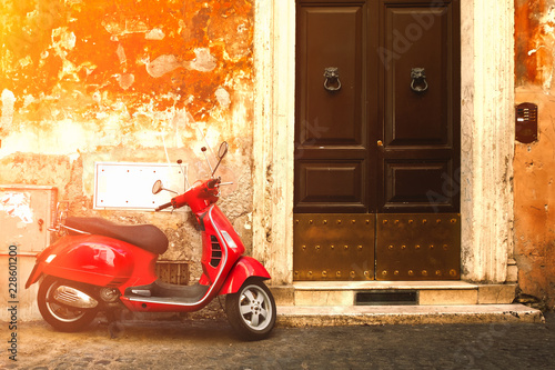 Red scooter on an old narrow street in Rome
