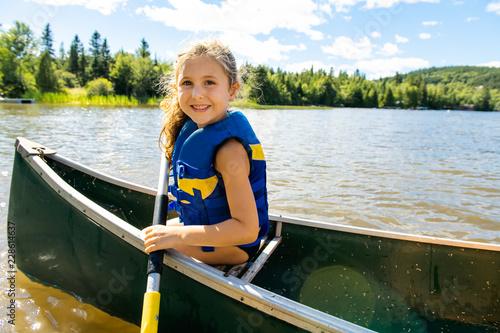 Happy kid enjoying canoe ride on beautiful river Fototapet