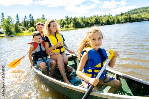 Leinwand Poster Family in a Canoe on a Lake having fun