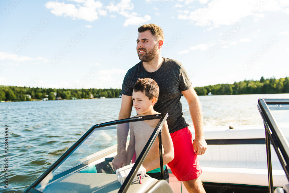 Fototapeta Man driving boat on holiday with his son kid