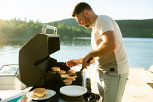 Father Preparing Hamburger On A Grill Outdoors Close To A Lake