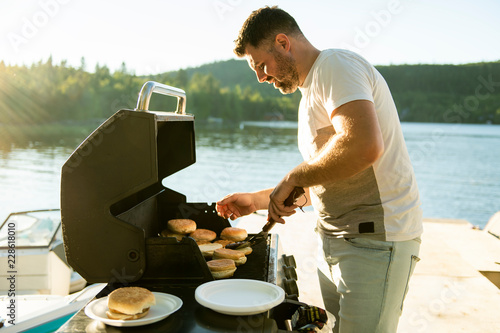 Canvastavla Father preparing hamburger on a grill outdoors close to a lake