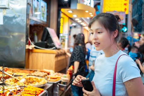 Fototapeta premium Dziewczyna próbuje lokalnego jedzenia ulicznego w Hongkongu - kulki rybne curry