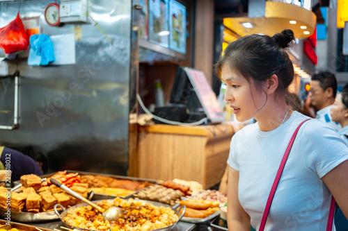 Tuinposter Aziatische Plekken Girl trying Hong Kong local street food - curry fish balls