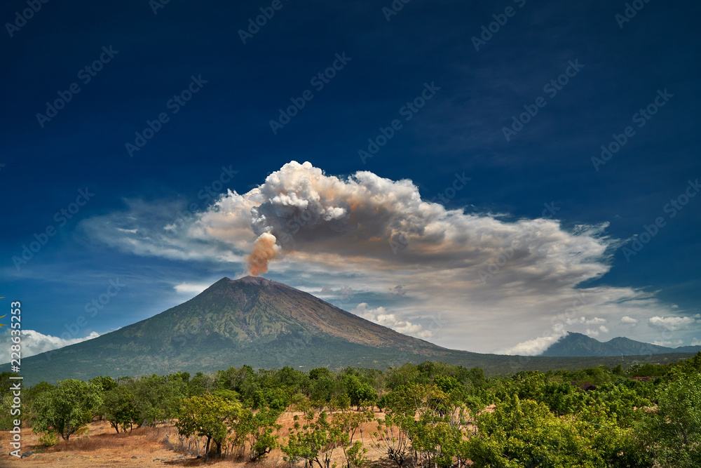 Fototapety, obrazy: 29 June 2018, Bali, Indonesia.Mount Agung volcano dramatic eruption over dark blue sky . Massive clouds of ash higlighted by magma.
