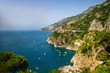 The view of Amalfi coast. This is on the south of Italy in Europe. The city stands on cliffs above the sea. There are boats on the sea.