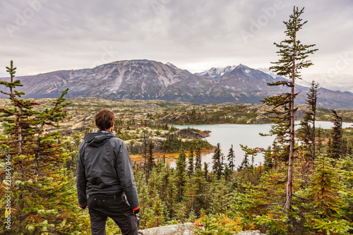Alaska hiking man travel outdoor lifestyle, Young traveler hiker at mountains landscape in autumn Wallpaper Mural