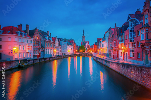 Foto op Canvas Brugge Scenic city view of Bruges canal with beautiful medieval colored houses, bridge and reflections in the evening, Belgium