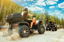 Two Quad Bike Riders In Helmets Travels In Forest