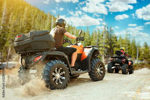 Cadres-photo bureau Motorise Two quad bike riders in helmets travels in forest