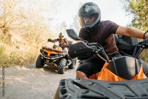 Foto op Canvas Motorsport Two quad bike riders travels in forest, front view