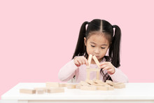 Young Little Cute Asian Girl Build A House From Wooden Block Construction, Wood Toy, Jenga House On Desk In Isolated Pink Background. Asia Children Play And Learn Creative Concept With Copy Space.