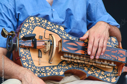 The wheel lyre in the hands of the playing musician. Canvas Print