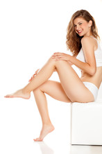 Young Happy Woman Applying Cream On Her Legs On White Background