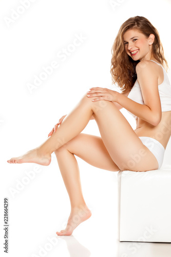 Obraz Young happy woman applying cream on her legs on white background - fototapety do salonu