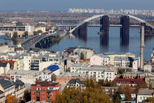 The Bridge, Which Is Being Repaired, Is On The Other Side Of The City. Beautiful View Of The City. Trees And Architecture. On Podol, Kiev. Ukraine.