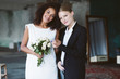 canvas print picture - Young pretty woman with blond hair in black suit and beautiful african american woman with dark curly hair in white dress with little bouquet of flowers happily looking in camera on wedding