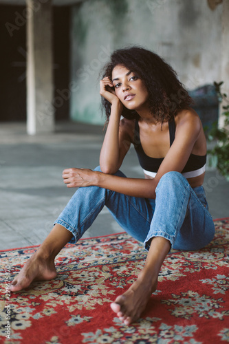 Black girl barefoot Beautiful African American Girl With Dark Curly Hair In Black Sporty Top And Jeans Thoughtfully Looking In Camera While Sitting On Vintage Carpet At Home Stock Photo Adobe Stock