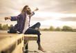 Leinwanddruck Bild - Young man sitting on a pier, feeling good