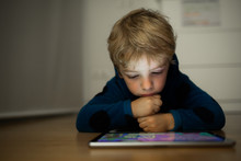 Caucasian Boy Watching Cartoons In A Tablet