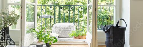Panoramic view of open balcony door, black bag, green plants and light grey pouf Fotobehang