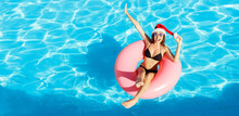Beautiful Happy Woman In Santa Claus Hat With Inflatable Ring Relaxing In Blue Swimming Pool