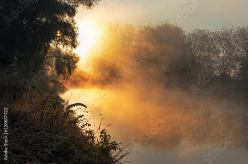 jaskrawy-pogodny-swiatlo-z-promieniami-i-cieniami-nad-mglowa-rzeka-przy-switem-mgla-unosi-sie-nad-woda-i-rozciaga-sie-na-wscho