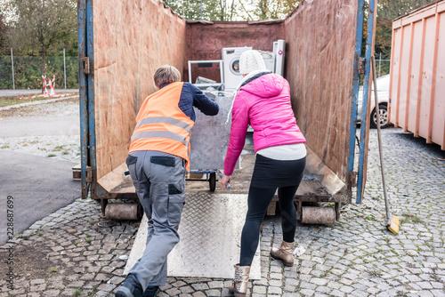 Wallpaper Mural Frau und Mann geben alte Elektrogeräte auf dem Wertstoffhof ab
