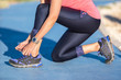 closeup of woman tying shoe laces. Female sport fitness runner getting ready for jogging outdoors