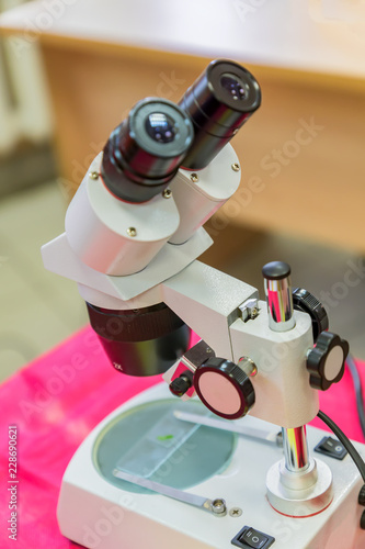 Fototapety, obrazy: Laboratory Equipment, Optical Microscope for school lessons on red table