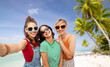 travel, tourism and vacation concept - group of happy female smiling friends in sunglasses taking selfie over tropical beach background in french polynesia