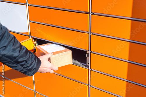 Fotografie, Obraz  Man putting box to parcel machine