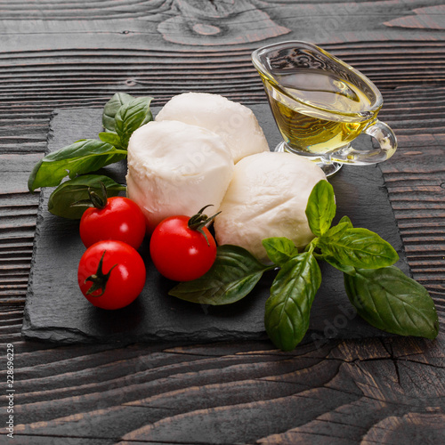 Poster Dairy products Mozzarella tomatoes and basil on a wooden rustic background