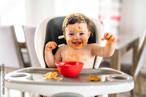 Fotomural child girl, eating spaghetti for lunch and making a mess at home in kitchen