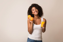 Excited Black Woman With Oranges And Juice