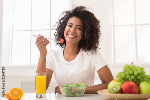 In de dag Kruidenierswinkel African-american woman with vegetable salad and fresh juice