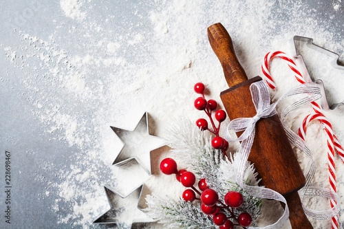 Bakery background for cooking christmas baking with rolling pin and scattered flour decorated with fir tree top view.