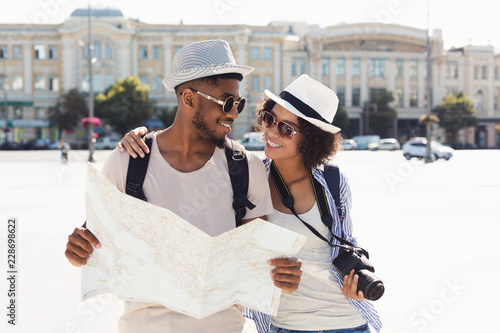 Loving african-american couple traveling and reading map in city Fototapet